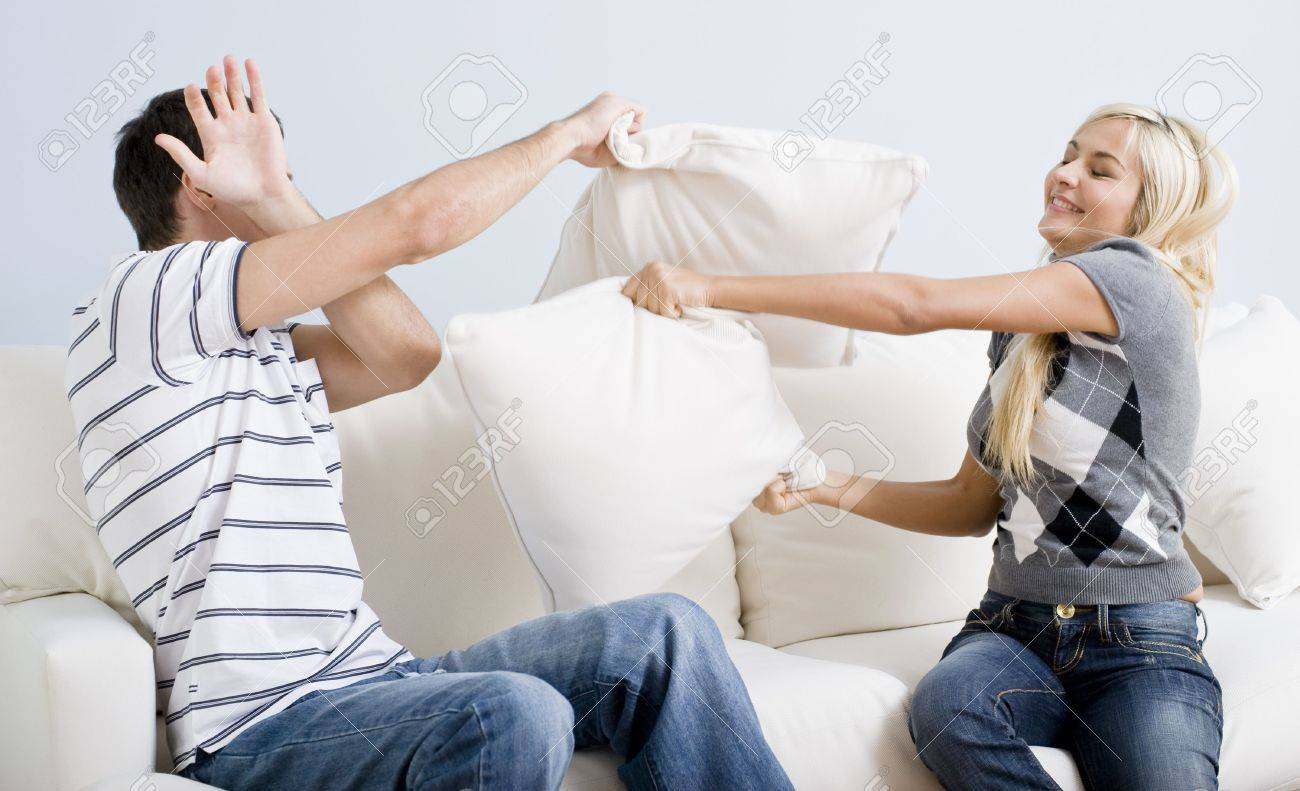 young man holds his arm up in defense as a young woman playful