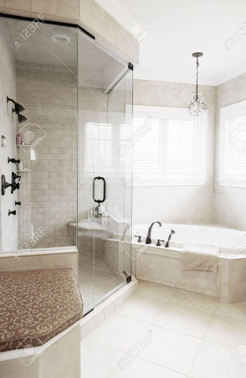 haut de gamme neutre attenue la salle de bains avec baignoire jacuzzi et douche format vertical