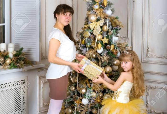 Mamá Le Da A Su Hija Un Regalo De Navidad Sobre El árbol Decorado De