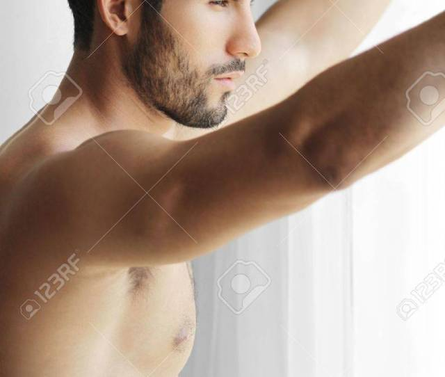 Portrait Of A Thoughtful Handsome Naked Young Man Looking Out Of A Window Thinking Stock Photo