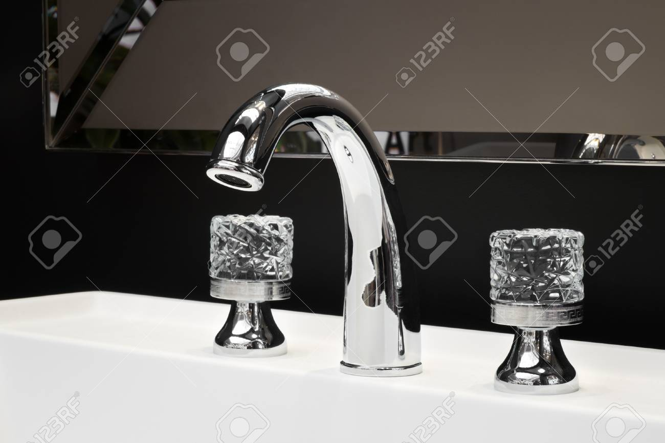 luxury faucet mixer with crystal handles on a white sink in a