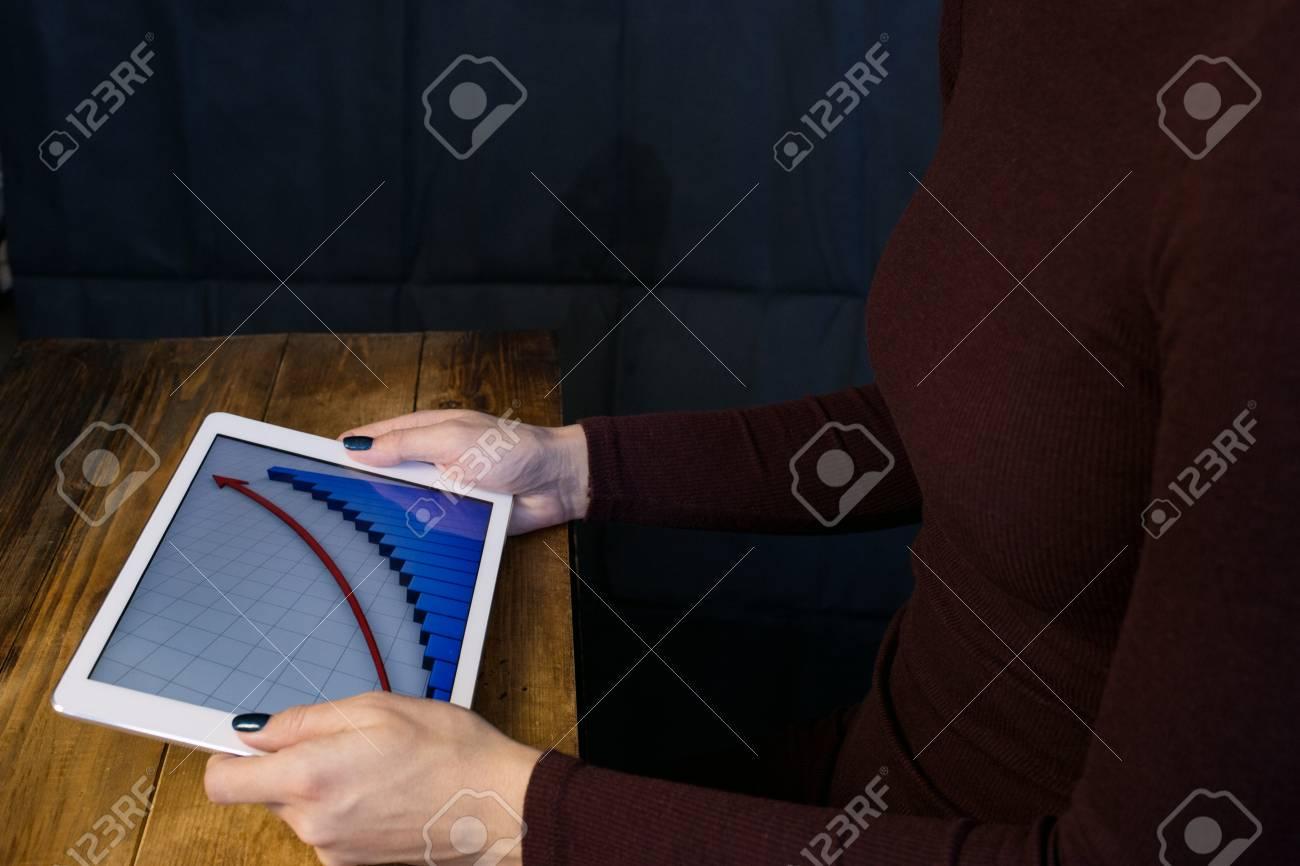 la fille qui travaille avec un ordinateur tablette le graphique se leve table en bois fond noir banque d images et photos libres de droits image 93326029