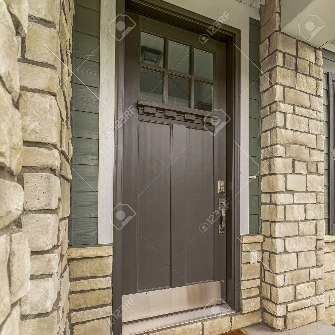 Square Home Entrance With A Glass Paned Brown Wooden Door And