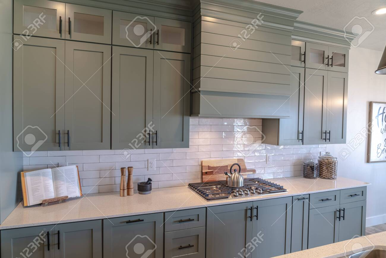 https www 123rf com photo 139152838 wooden cabinets and white counter top inside a kitchen with tile backsplash kitchen island sink and html