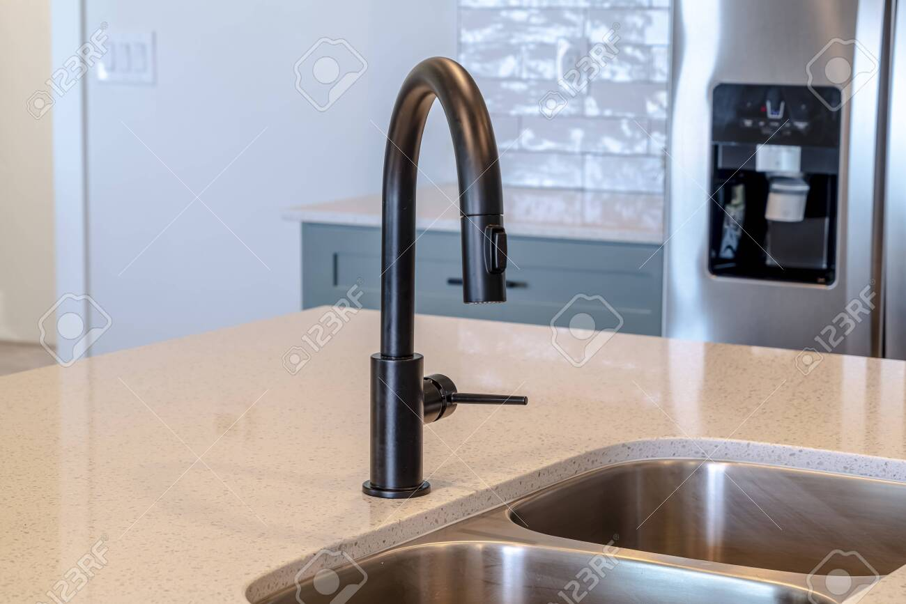 https www 123rf com photo 139152756 black faucet and stainless steel double basin sink on the home kitchen island refrigerator with ice html