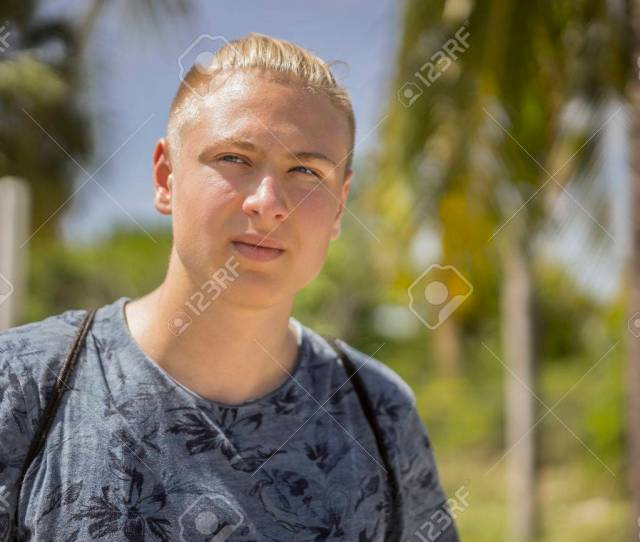Stock Photo Thoughtful Blond Teenager With His Hair Tied Up Standing Staring At The Camera While Standing Outdoors In Tropical Sunshine With Palm Trees