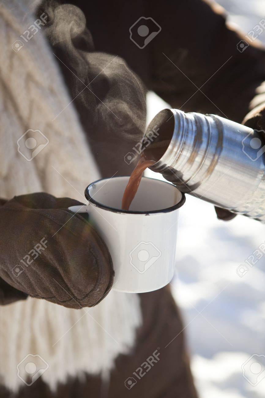 verser le chocolat chaud a partir d un thermos pour une tasse sur une journee d hiver en plein air