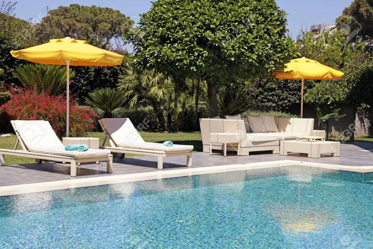 mobilier d exterieur blanche dans le jardin pres de la piscine pour se detendre sur la belle station balneaire