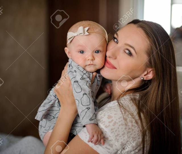 Stock Photo Young Brunette Mom Holding Her Little Blondie Daughter On Hands Close To Face In Their Home On The Blurred Background