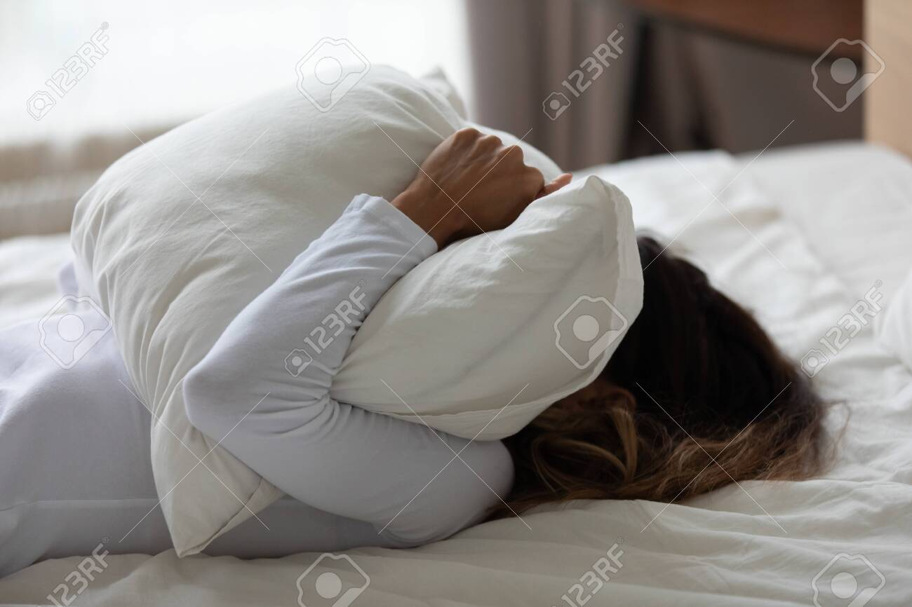 close up girl cover face with cushion sobbing inconsolably into
