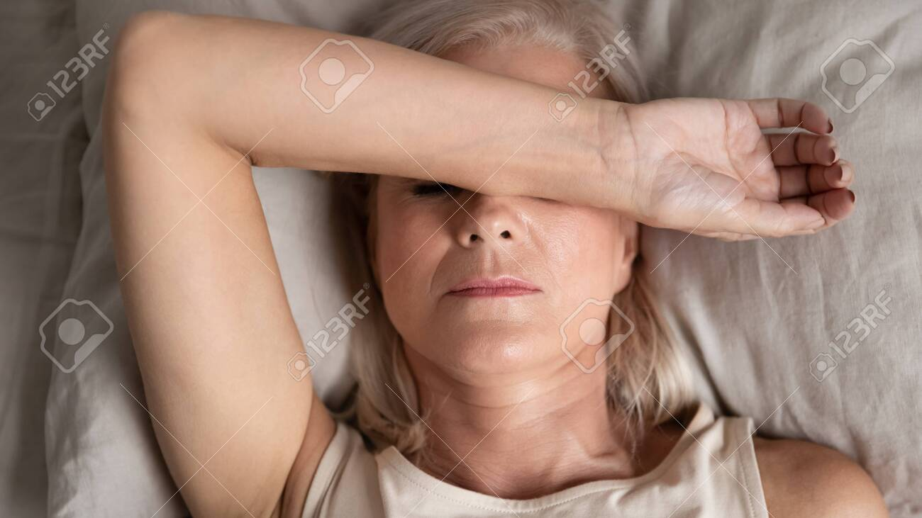close up top view middle aged woman lying down in bed on pillow