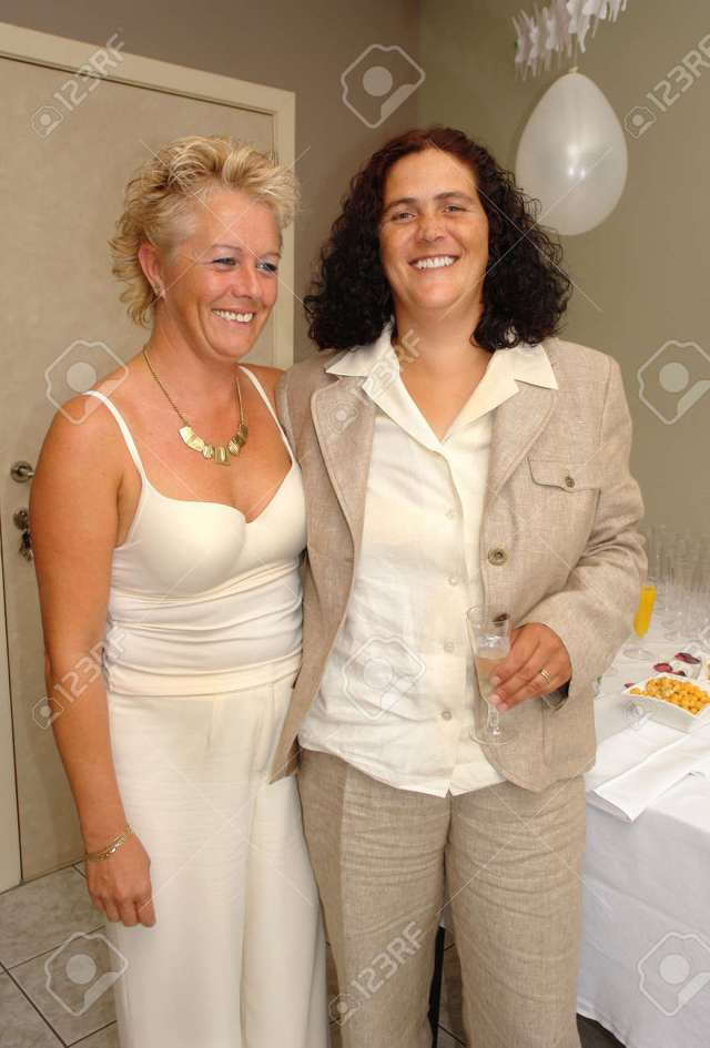 Lesbian Mature Couple Posing And Celebrating With Champaign At Their Wedding Party After The Official Marriage