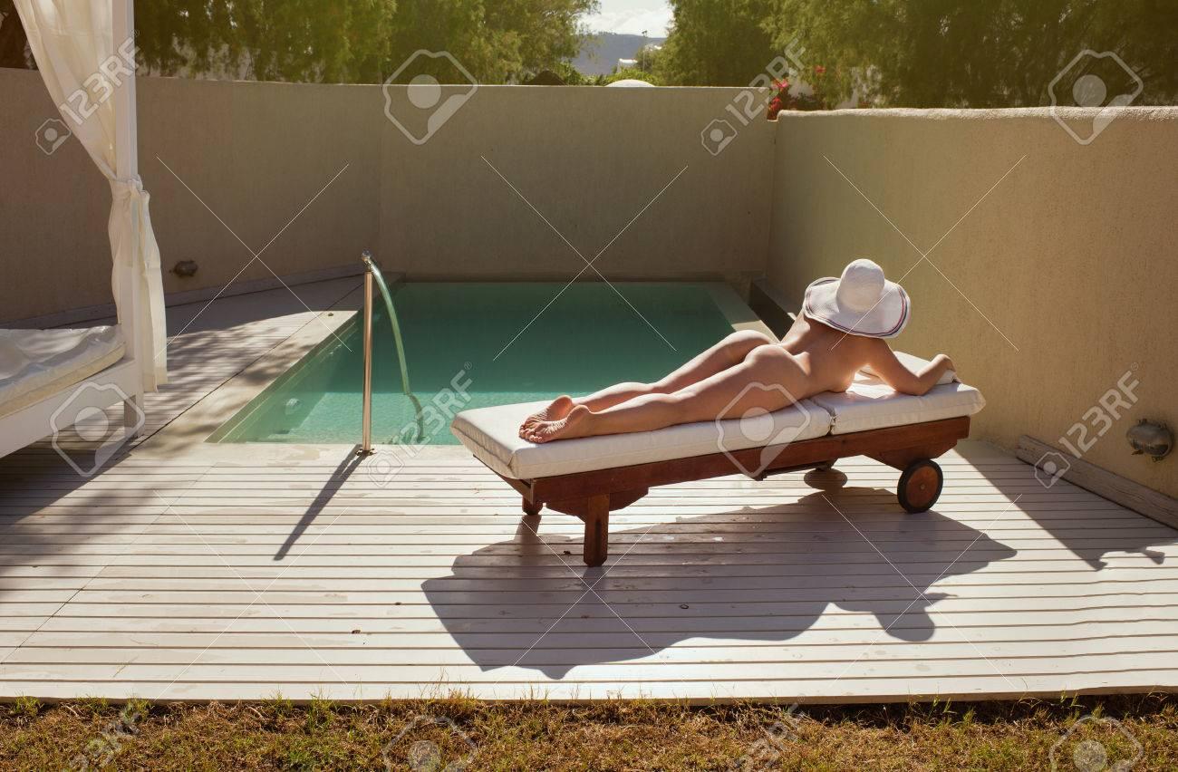 belle fille nue est allongee sur un transat au bord de la piscine et bronzer au coucher du soleil