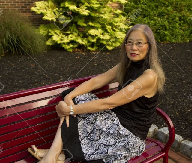 Mature Senior Asian Woman Seated On A Red Metal Bench Has Feet Up To Take