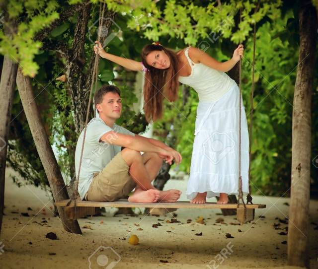 Stock Photo Young Romantic Couple Swinging In Tropical Park