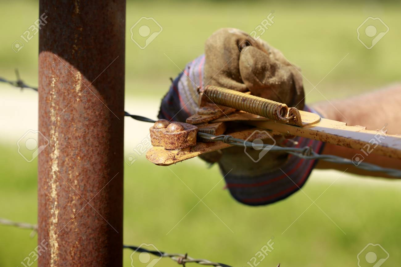Fencing Man Working On Old Barb Wire Farm Fence With Hand Fence Stock Photo Picture And Royalty Free Image Image 75226606