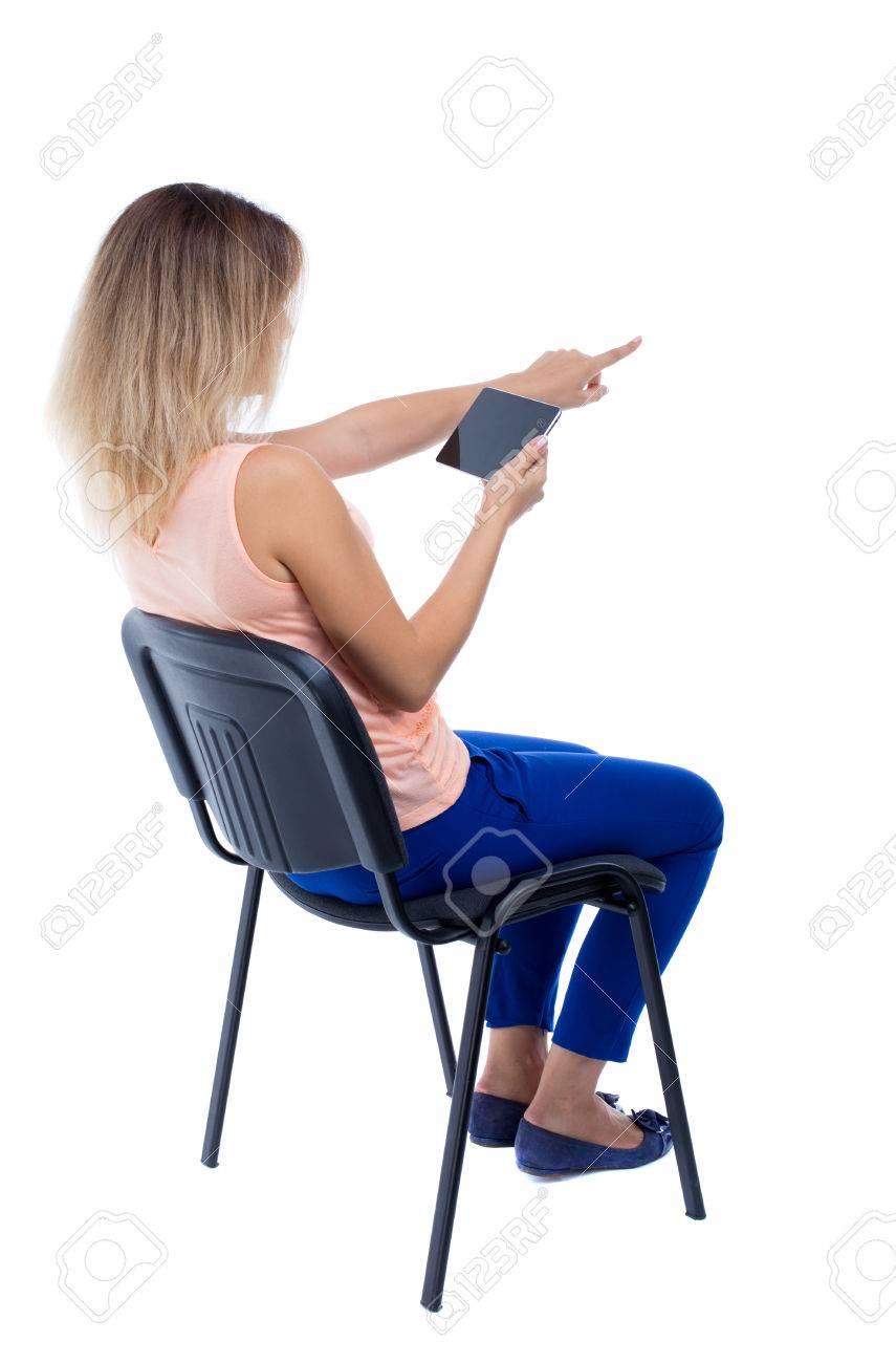 vue de dos de pointage femme assise sur une chaise et regarde l ecran de la tablette arriere collection vue de personnes backside vue de la personne isole sur fond blanc blonde dans
