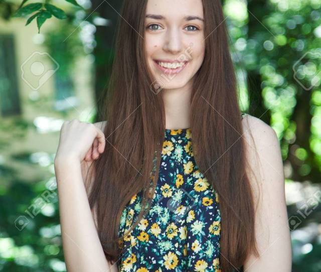 Stock Photo Young Beautiful Brown Haired Teen Girl With Long Hair Smiling At The Camera In A Summer Park