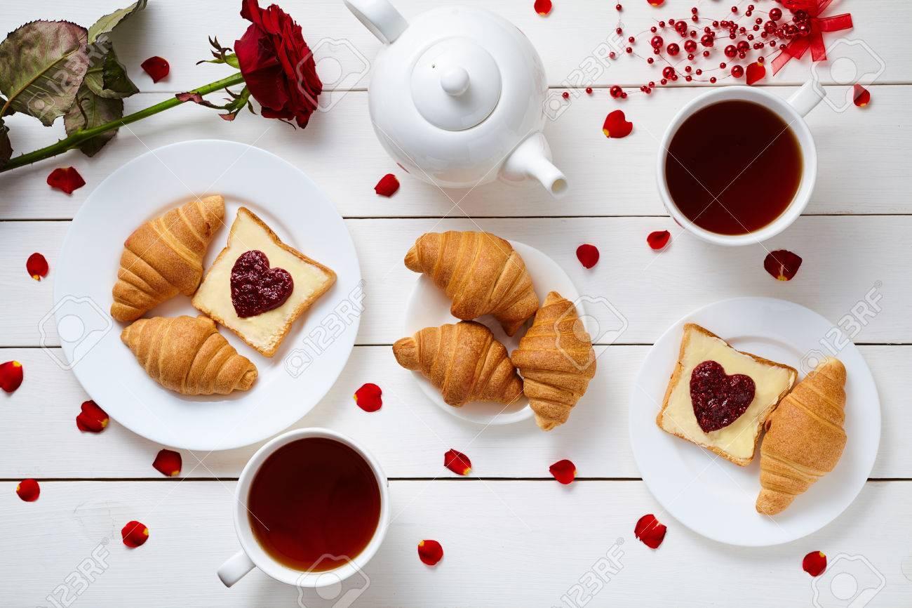 petit dejeuner romantique pour la saint valentin avec des toasts en forme de coeur de la confiture des croissants des petales de rose et de the sur blanc table en bois fond concept