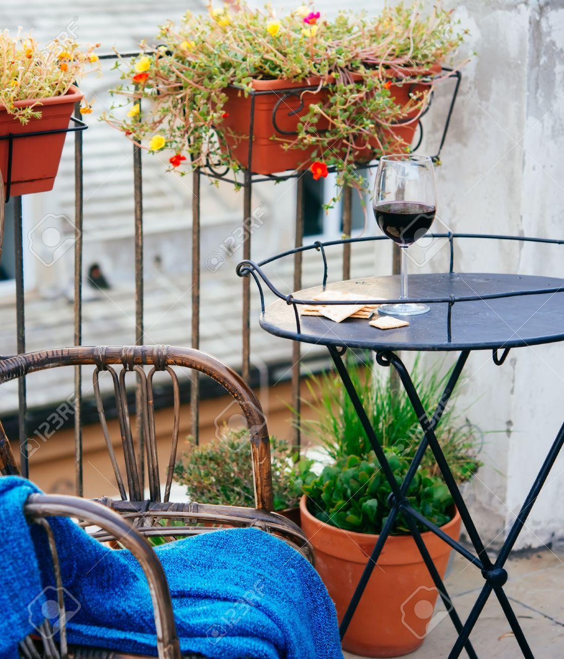belle terrasse ou balcon avec petite table en fer chaise et verre a vin