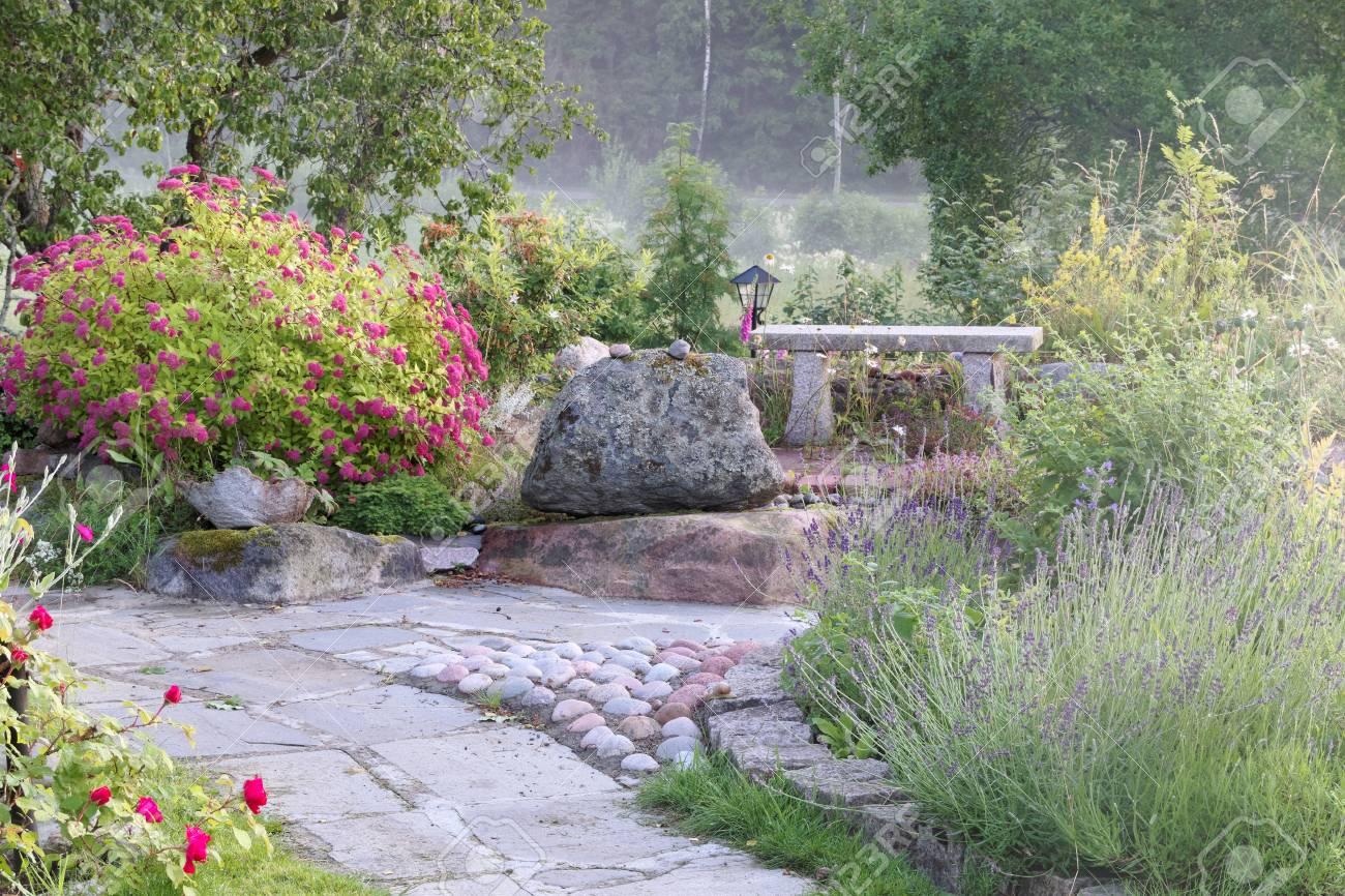 beau jardin avec plats roses et bleus un banc de pierre et une allee en pierre d ardoise banque d images et photos libres de droits image 43418902
