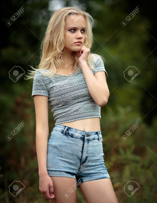 Location Portrait Of A Beautiful Young Blond Teenage Girl Alone In The Woods Wearing Denim Shorts