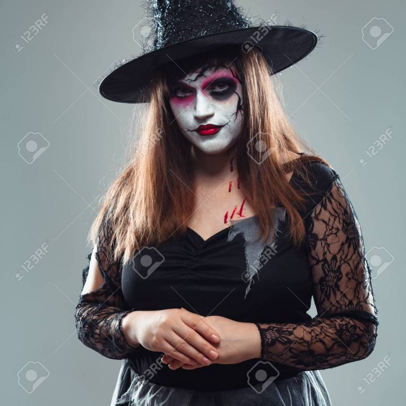 Gothic Young Woman In Witch Halloween Costume With Hat Standing Over Gray Background