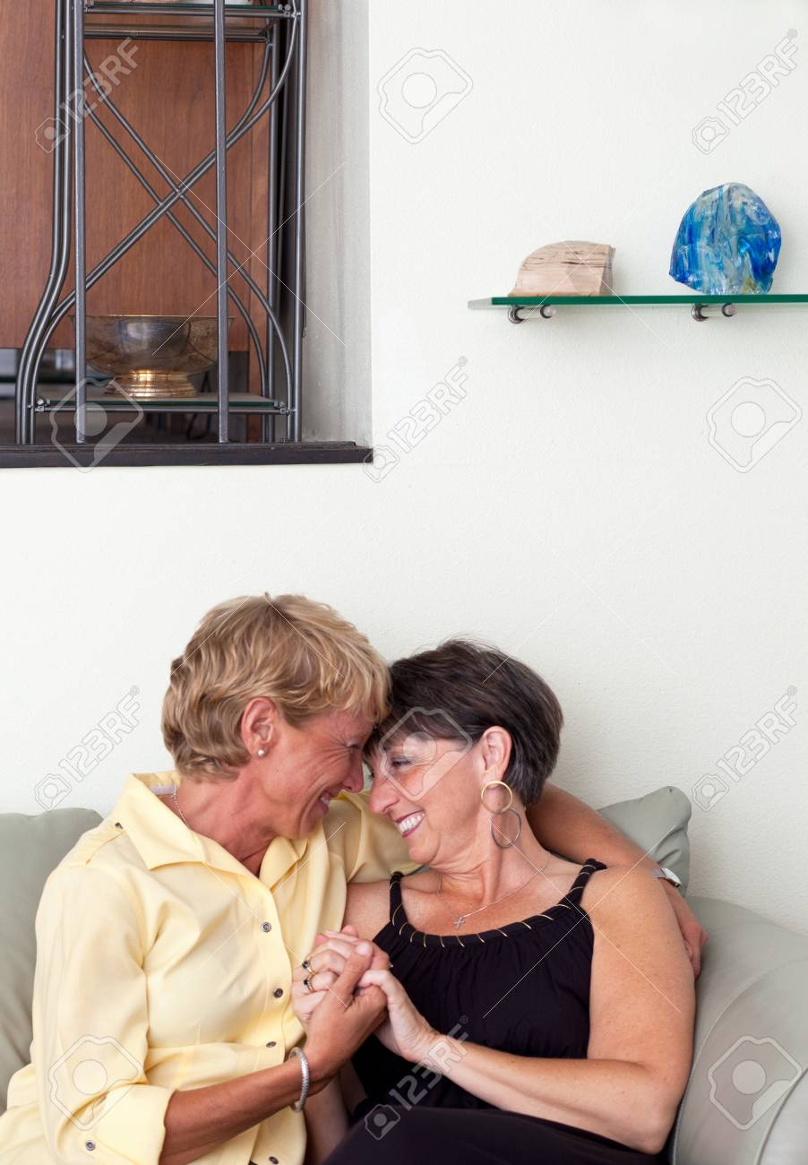 Mature Lesbian Couple Embracing On Sofa Stock Photo 86289733