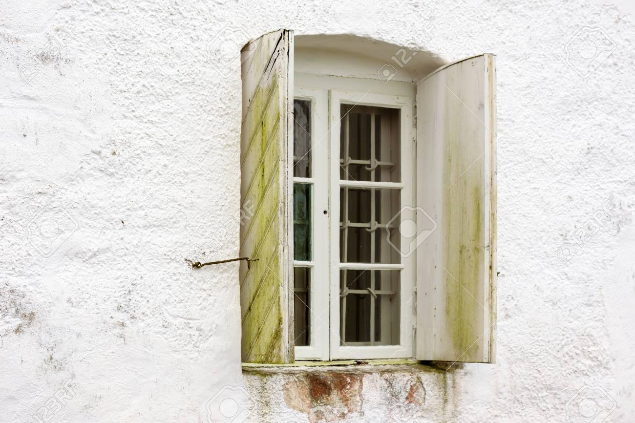 An Old Window With Iron Bars On The Inside And Open Wooden Window