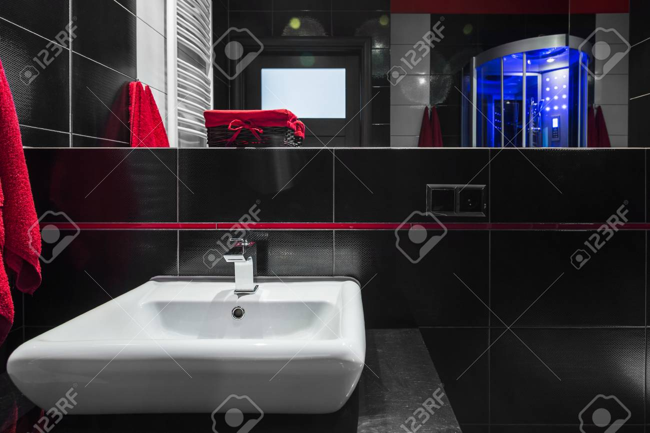 salle de bain moderne avec carrelage mural noir grand miroir et evier blanc