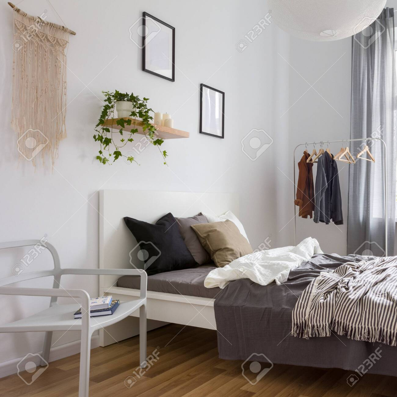 simple bedroom with double bed clothes rack and wall decoration stock photo picture and royalty free image image 128424193