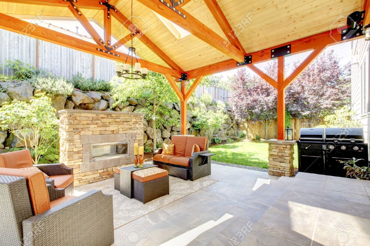 exterior covered patio with fireplace and furniture wood ceiling