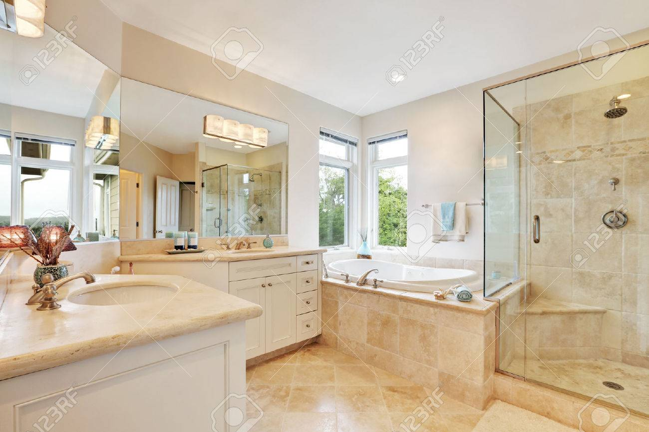 maitre interieur de salle de bain avec carrelage beige double lavabo baignoire et douche en verre nord ouest etats unis