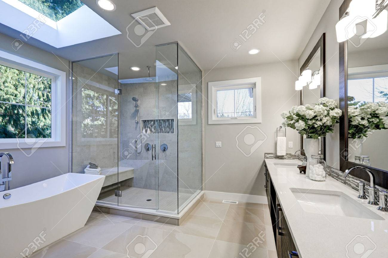 salle de bain spacieuse dans les tons gris avec planchers chauffants baignoire autoportante douche a l italienne lavabo double vasque et puits de