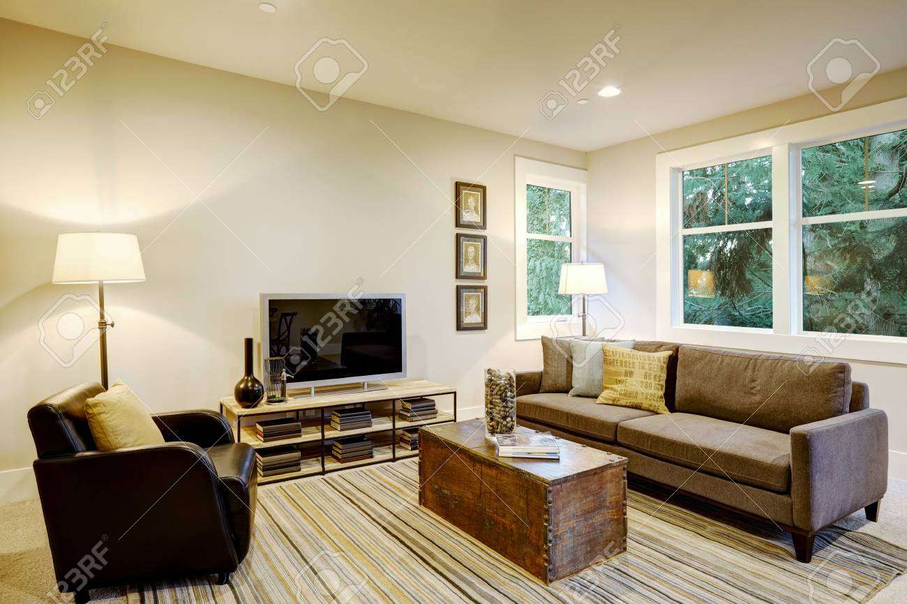 family room interior with gray sofa facing a black leather armchair