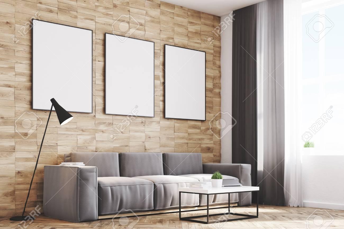 vue de cote d un salon avec des murs en bois clair un long canape et trois affiches verticales encadrees au dessus rendu 3d maquette