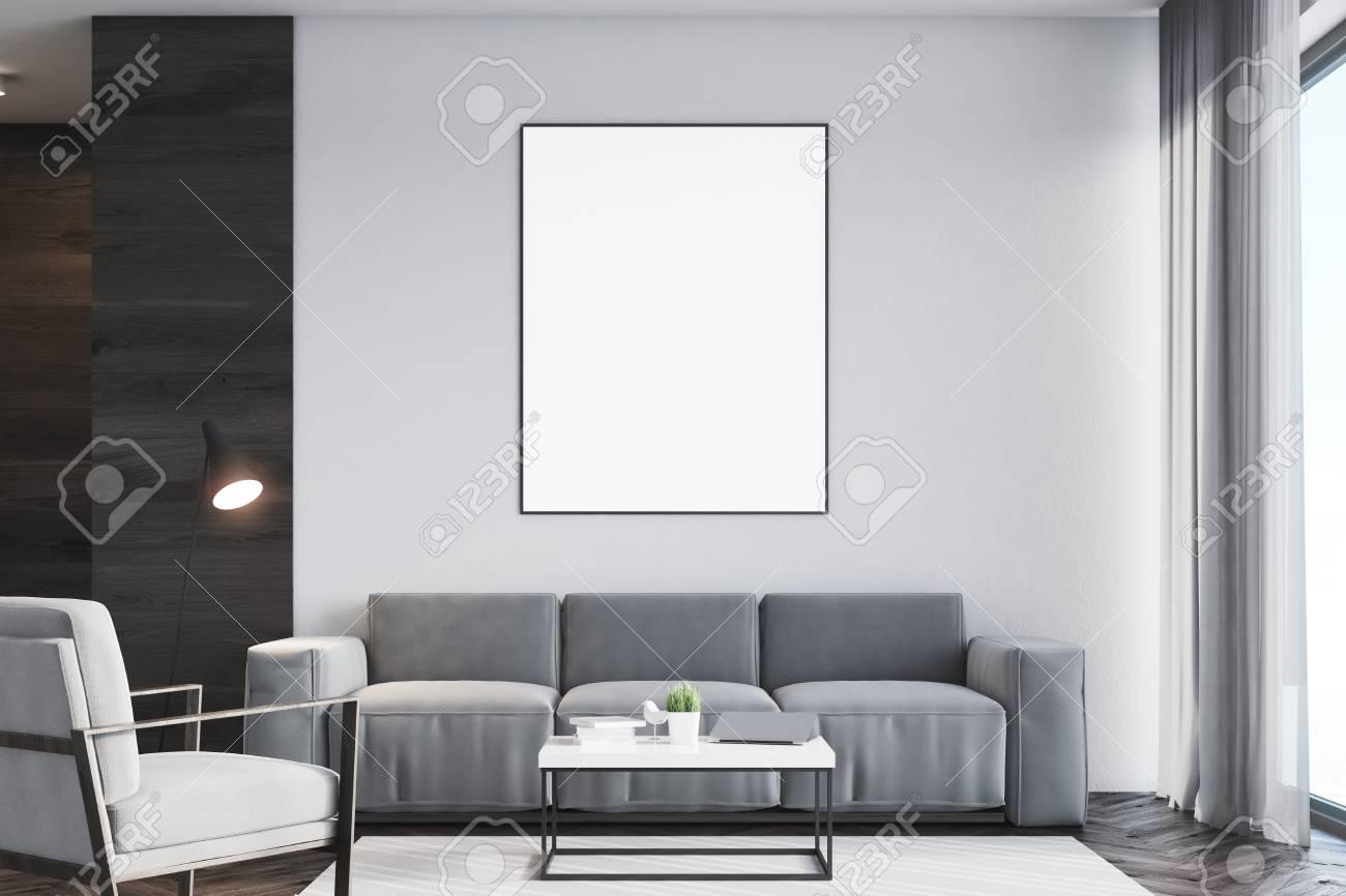 interieur de salon avec un fragment de mur noir un fauteuil gris un canape une table basse et une grande affiche verticale encadree rendu 3d