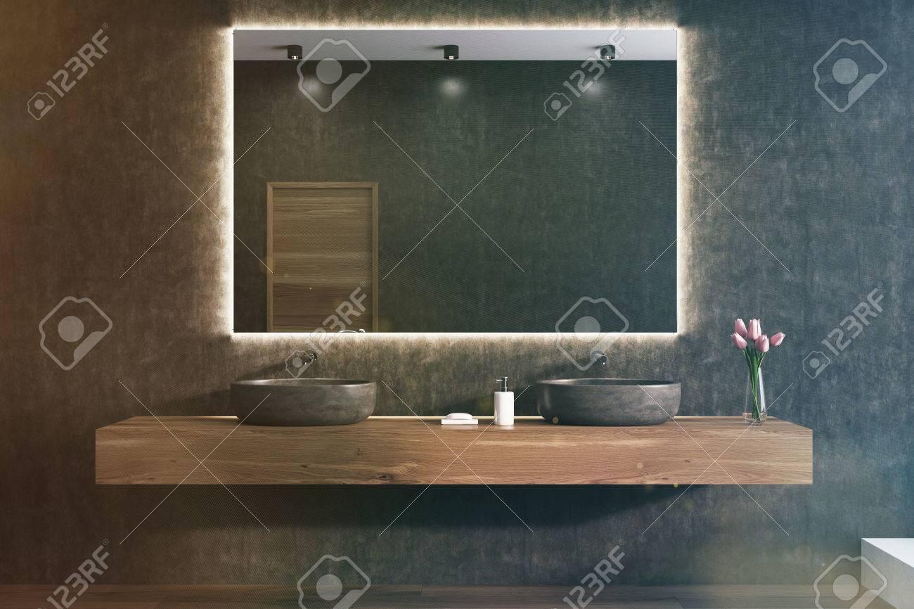 grand miroir horizontal est accroche sur un mur de salle de bain noir il y a deux lavabos sur une etagere en bois en dessous et un vase de fleurs