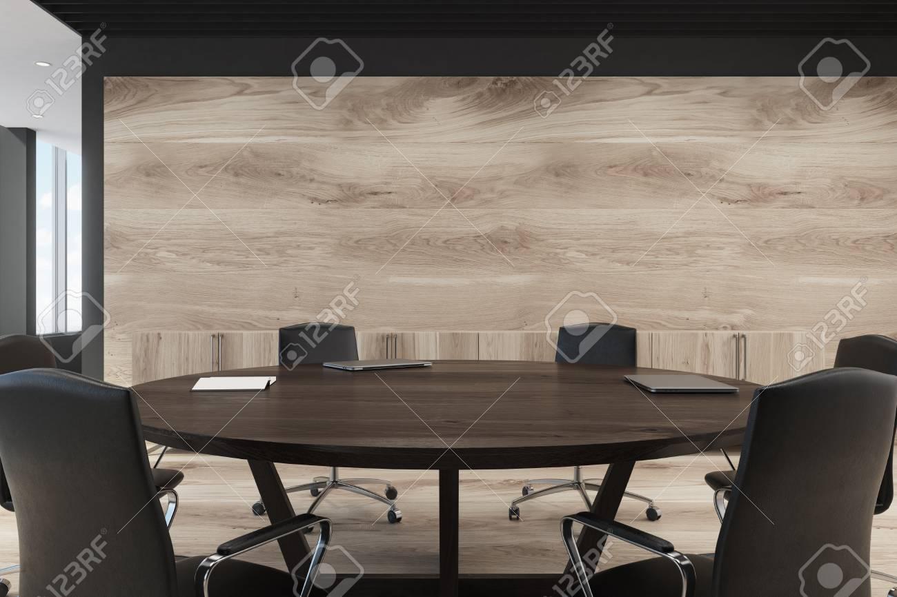 bureau avec une grande table ronde noire des chaises et des murs en bois clair lobby avec des fenetres panoramiques sur la gauche maquette 3d