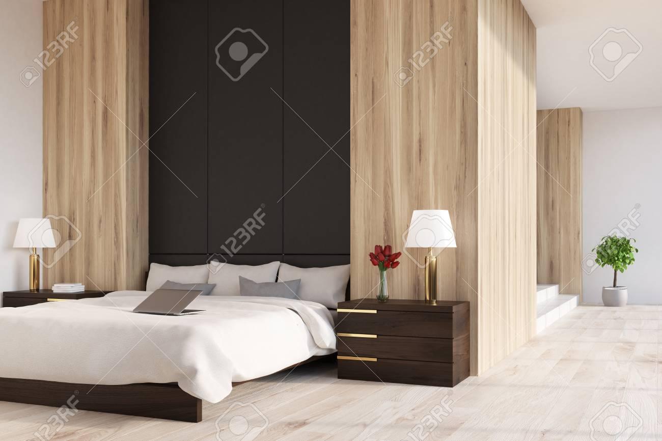 interieur de chambre a coucher en bois avec un fragment de mur noir un plancher en bois et une fenetre panoramique un lit double avec deux tables de