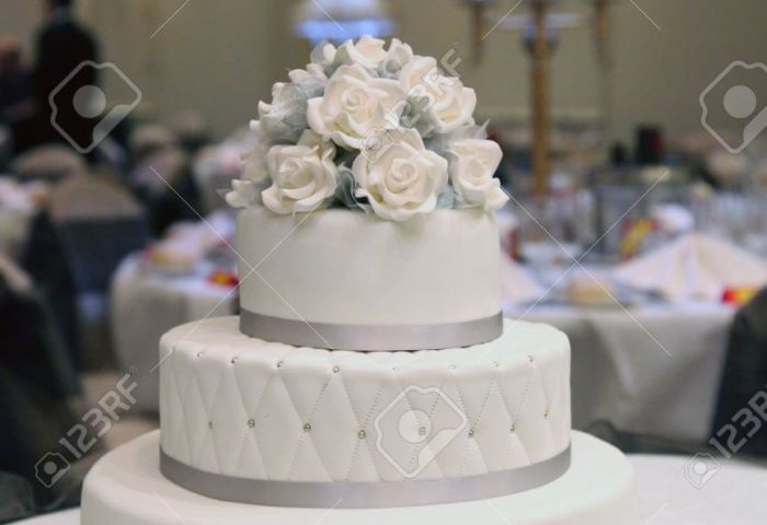 A White Wedding Cake With White Icing Roses