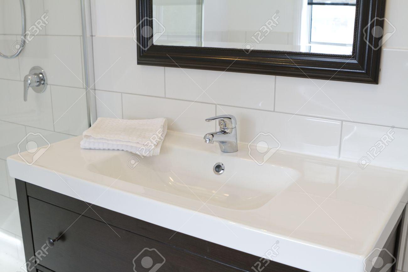 Black Bathroom Vanity And Mirror In A Contemporary Bathroom