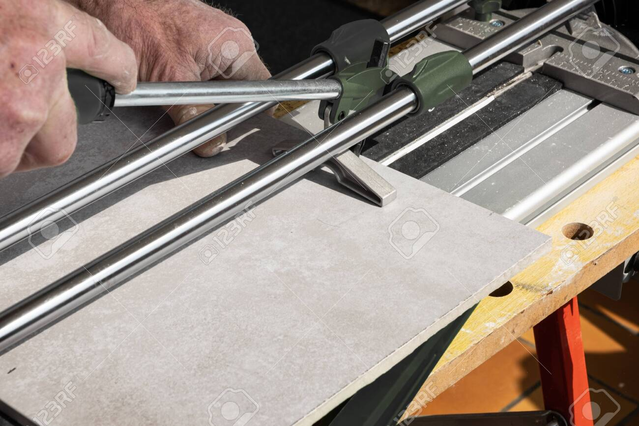the mason cuts a ceramic tile with a tile cutter stock photo picture and royalty free image image 138026530