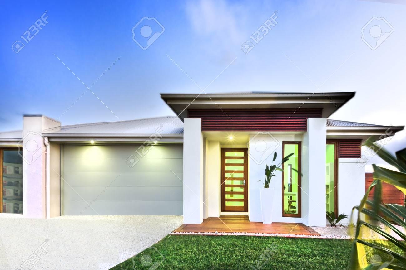 maison moderne a une belle pelouse devant la maison et le garage du cote gauche qui a cour en beton les lumieres sont allumees sous le toit il y a beaucoup d elements