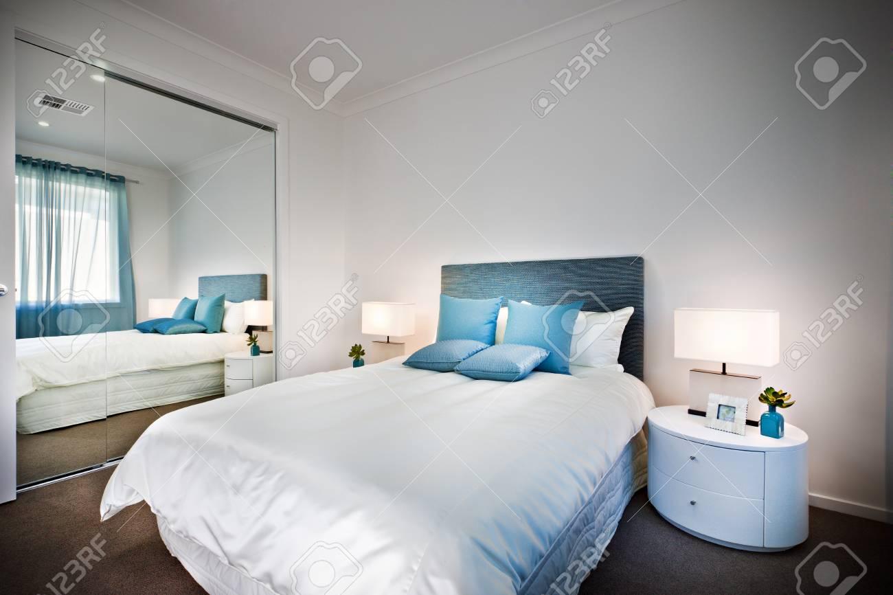 banque d images lit avec un grand miroir a cote d une lampe et une table qui est de forme arrondie les draps sont blancs avec des oreillers bleus pres de