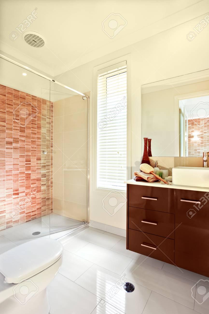 salle de bain de luxe a des carreaux de sol blanc exposes a la lumiere du soleil le meuble en bois brun a des tiroirs et un comptoir avec lavabo devant le
