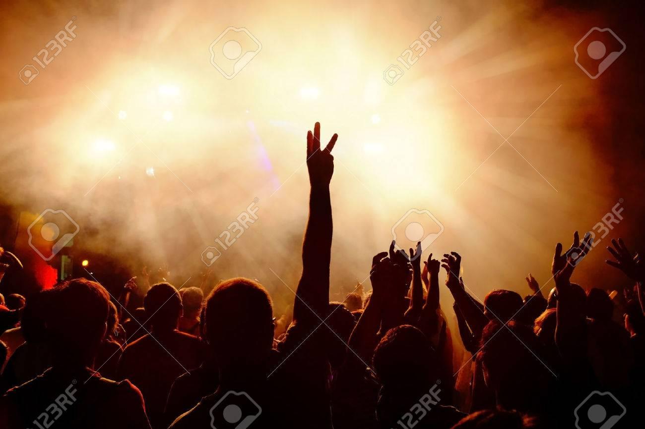 silhouettes de foule festive de jeunes dansant au festival de musique main levee contre fume fond orange avec des faisceaux lumineux