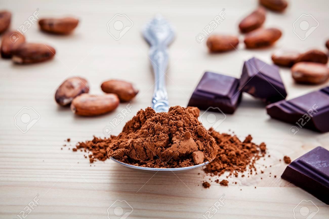 poudre de chocolat brun dans la cuillere feves de cacao roties et la configuration de chocolat noir sur fond en bois profondeur de mise au point