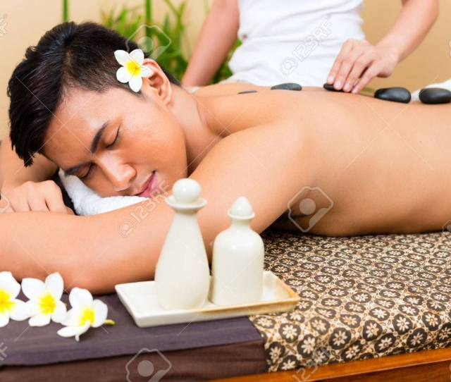 Indonesian Asian Man In Wellness Beauty Day Spa Having Hot Stone Massage Or Treatment Looking