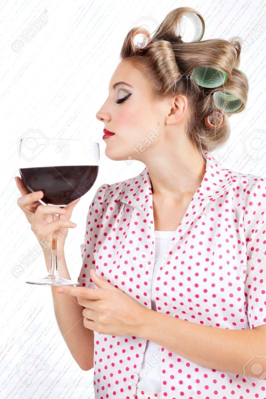 jeune femme avec bigoudis ayant de verre geant de vin rouge